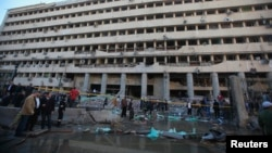Petugas kepolisian dan warga berkumpul di depan markas polisi yang rusak pasca serangan bom di Kairo (24/1)