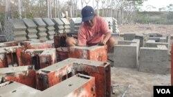 Seorang tukang sedang membuka cetakan panel beton p3 yang digunakan sebagai siku sambungan untuk kebutuhan hunian risha. (Foto: VOA/Yoanes Litha)