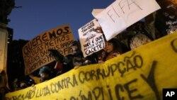 "Para demonsran membentangkan spanduk bertuliskan ""Kami ingin sekolah, kereta api, bus, kapal feri dan rumah sakit berkualitas FIFA"" dan spanduk mengecam pemain sepakbola Ronaldo, mantan pesepak bola andalan Brazil di Rio de Janeiro, Brazil (30/5)."