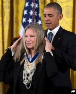 ປະທານາທິບໍດີ ສະຫະລັດ ທ່ານ Barack Obama (ຂວາ) ມອມຫຼຽນໄຊ ເສລີພາບ ຂອງປະທານາທິບໍດີ ໃຫ້ແກ່ ທ່ານນາງ Barbra Streisand ໃນລະຫວ່າງພິທີມອບ ຢູ່ທີ່ວໍຊິງຕັນ ເມື່ອວັນທີ 24 ພະຈິກ 2015, ໃນຫ້ອງກ້ຳຕາເວັນອອກ ຂອງທຳນຽບຂາວ.