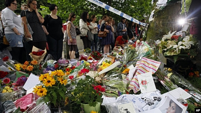 Fans gather around flowers and tributes near the home of British singer Amy Winehouse in London, July 25, 2011