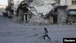 ເດັກນ້ອຍແມ່ຍິງຄົນນຶ່ງ ຍ່າງກາຍອາຄານ ທີ່ໄດ້ຮັບ ຄວາມເສຍຫາຍ ຢູ່ເມືອງ Maaret al-Numan ແຂວງ Idlib.