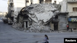 A girl runs past damaged buildings in the rebel-controlled area of Maaret al-Numan town in Idlib province, Syria, Dec. 21, 2015.