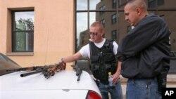 Les policiers de l'Université du Nouveau-Mexique Robert Rush (g) et Ernesto Pacheco regardent les armes trouvées au domicile de l'étudiant Kevin Boyar mardi 6 mai 2008 à Albuquerque. K. Boyar a été arrêté pour avoir transporté illégalement des armes sur le campus.