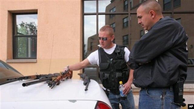 Polisi kampus Universitas New Mexico Robert Rush (kiri) dan Pacheco Ernesto mengamati senjata-senjata yang ditemukan di kediaman mahasiswa Kevin Boyar di Albuquerque, N.M. Boyar ditangkap atas tuduhan secara tidak sah membawa senjata ke kampus (foto: dok).