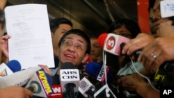 Maria Ressa, left, the award-winning head of a Philippine online news site Rappler that has aggressively covered President Rodrigo Duterte's policies, shows her release order after posting bail, Feb. 14, 2019 in Manila, Philippines.