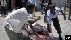 4月4号索马里国家剧院前发生爆炸,人们用担架把伤员抬走