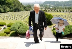 FILE - Ju Hong-jang, 81, and his wife Yoon Bok-hee, 73, visit a gravestone of his father, Ju Bong-gyeom, a police officer who died in 1952 during the Korean War, at the National Cemetery in Seoul, June 23, 2010. Ju's father took part in a bloody suppression operation to clear anti-government protesters and communists on Jeju island.