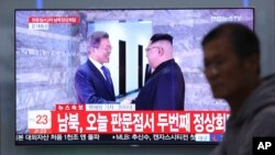 A TV screen shows South Korean President Moon Jae-in, left, meeting with North Korean leader Kim Jong Un at the border village of Panmunjom during a news program at the Seoul Railway Station in Seoul, South Korea, May 26, 2018.