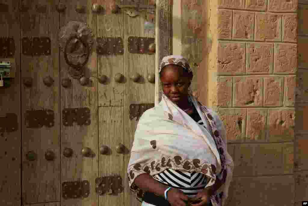 Cette photo de mai 2012 montre une femme devant une porte traiditionnelle décorée de Tombouctou.