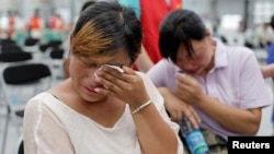 Family members cry at a caring centre for relatives of victims of a factory explosion, in Kunshan, Jiangsu province, August 3, 2014.