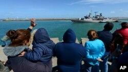 """Warga dan keluarga awak kapal selam Argentina di pangkalan Mar del Plata melambai kepada awak kapal perusak """"Sarandi"""" yang bergabung untuk melakukan pencarian kapal selam yang hilang (21/11)."""