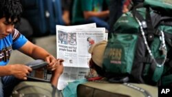 A newspaper shows news about people leaving the city at a railway station in Bangalore, India, Aug. 16, 2012