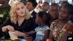 FILE - US musician Madonna, left, sits with her adopted children Stella, David and Mercy, at the opening of The Mercy James Institute for Pediatric Surgery and Intensive Care, located at the Queen Elizabeth Central Hospital in the city of Blantyre, Malawi