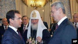 Russian President Dmitry Medvedev, (L) new Moscow Mayor Sergei Sobyanin (R) and Russian Orthodox Patriarch Kirill (C) toast after an inauguration ceremony in Moscow, 21 Oct 2010