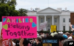 FILE - Activists march past the White House to protest the Trump administration's approach to illegal border crossings and separation of children from immigrant parents in Washington, June 20, 2018.