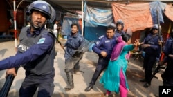 A Bangladeshi garment worker clashes with policemen during a protest in Savar, on the outskirts of Dhaka, Bangladesh, Jan. 9, 2019.