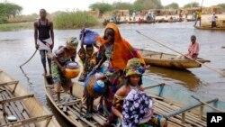 Des femmes peuls traversent un affluent du lac Tchad au village de N'Gouboua, le jeudi 5 Mars, 2015. (AP Photo / Jerome Delay)