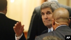U.S. Secretary of State John Kerry, set to participate in talks on Syria, waves as he arrives at a hotel in Vienna, Nov. 13, 2015.