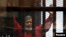 Tư liệu - Cựu Tổng thống Ai Cập Mohammed Mursi trong một lần xuất hiện trước tòa án cùng những thành viên của tổ chức Huynh đệ Hồi giáo ở ngoại ô Cairo, ngày 21 tháng 6, 2015.