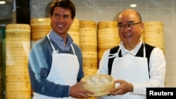 Aktor Tom Cruise berpose bersama Presiden Din Tai Fung Yang Chi-hua dan xiaolongbao, atau dumpling alias pangsit khas restoran tersebut (6/4).