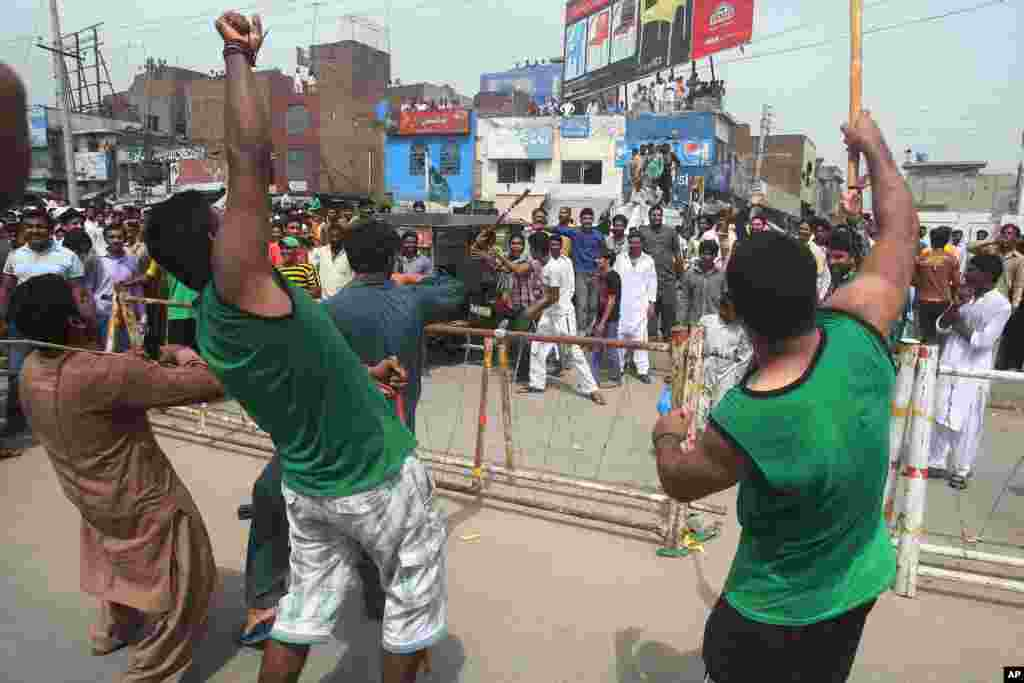 Supporters of Pakistan's cricketer-turned-politician Imran Khan, in green shirts, clash with supporters of the ruling party in Gujranwala, Pakistan, Aug. 15, 2014.