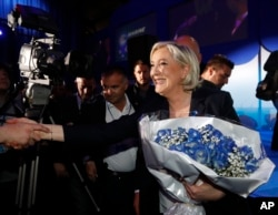 French far-right leader Marine Le Pen celebrates with supporters while holding a bouquet of flowers at her election day headquarters in Henin-Beaumont, northern France, April 23, 2017.