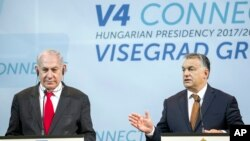Israeli Prime Minister Benjamin Netanyahu, left, listens to Hungarian Prime Minister Viktor Orban during a press conference held after the talks of Netanyahu with heads of government of the Visegrad Group in the Pesti Vigado building in Budapest, Hungary, July 19, 2017.