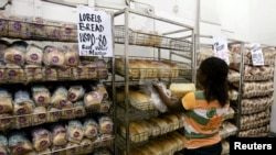 FILE - A worker arranges bread for sale inside a supermarket in Harare, March 26, 2009.