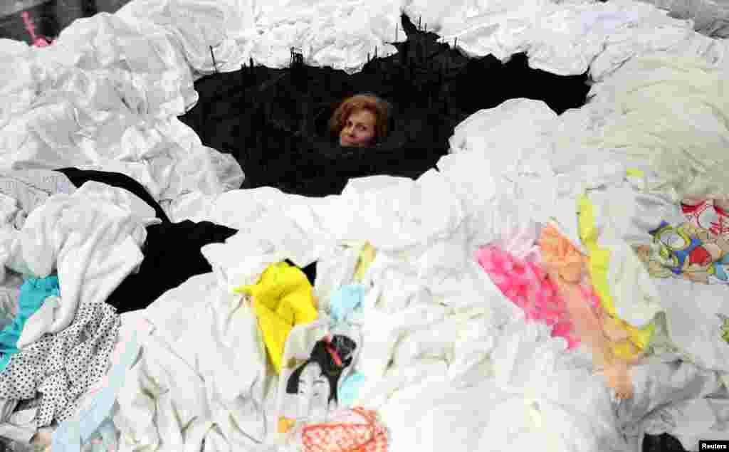 អ្នកទេសចរម្នាក់កំពុងសម្លឹងមើលការរៀបចំសិល្បៈដែលគេដាក់ឈ្មោះថា «លើសពីភាពគ្មានសណ្ដាប់ធ្នាប់» របស់សិល្បករTakahiro Iwasaki នៅក្នុងទីតាំងសម្រាប់ក្រុមការងារមកពីប្រទេសជប៉ុន នៅកម្មវិធីតាំងពិព័រណ៍ La Biennale នៅ ទីក្រុងVenice ប្រទេសអ៊ីតាលី។