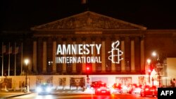 The logo of NGO Amnesty International is projected onto the Palais Bourbon, the seat of the French national assembly, late on June 18, 2018.