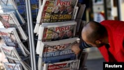 FILE - A man looks at newspapers at a kiosk in Diyarbakir, Turkey, following Sunday's elections, Nov. 2, 2015.