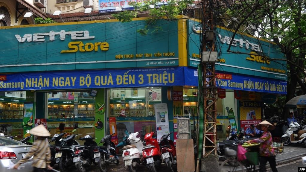 Một người bán hàng rong đi ngang một cửa hàng Viettel ở Hà Nội.