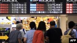 Calon penumpang melihat papan pengumuman di stasiun Osaka. Kereta ditunda keberangkatannya hingga tiga jam akibat Topan Nangka (17/7).