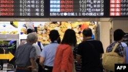 17일 태풍 낭카가 일본 서부 지역을 강타한 가운데, 열차 운행이 지연된 오사카 기차역에서 승객들이 전광판 안내문을 읽고 있다.