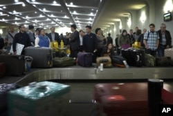 FILE - Passengers wait for their luggage upon arrival at the Sunan International Airport in Pyongyang, North Korea, Oct. 21, 2014.