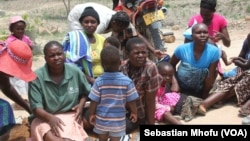 Women and their children in Mutare West wait as food is being cooked in December 2015 under FAO's Livelihoods and Food Security Program in Zimbabwe.