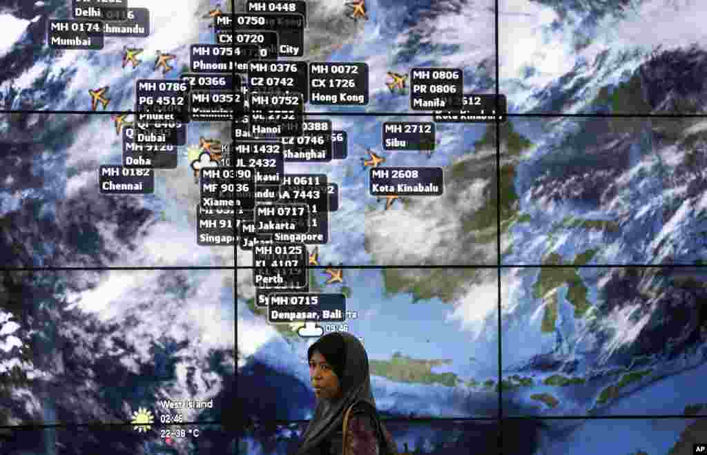 A woman stands in front of an electronic display showing live information at the Kuala Lumpur International Airport, March 16, 2014.
