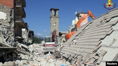f8558624024d1a Rescuers work at a collapsed house following an earthquake in Amatrice