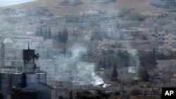 Kepulan asap terlihat membumbung di atas kota Kobani, menyusul pertempuran antara Pasukan Kurdi di Suriah dan militant ISIS dilihat dari puncak bukit di wilayah Suruc, perbatasan Turki-Suriah (21/10).