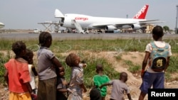 FILE - A humanitarian plane of the World Food Program (WFP) unloads sacks of cereal at Mpoko international airport in Bangui, which is located near a camp for displaced people.
