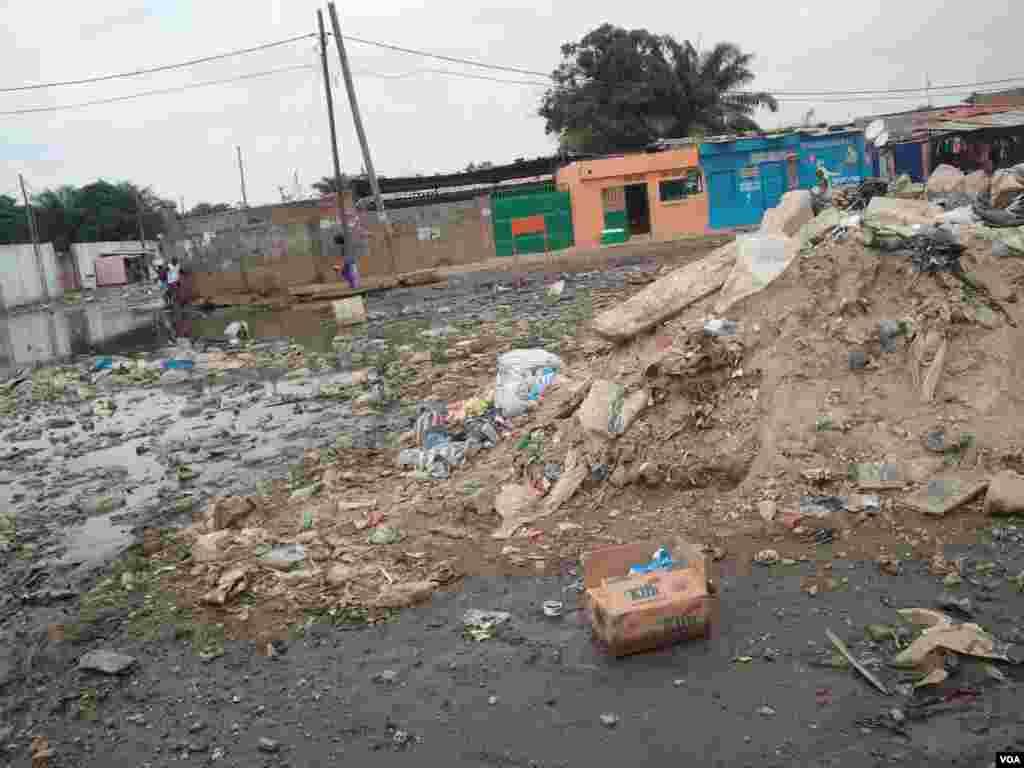 Angola, Luanda. Moradores tentam chegar ao seu destino, evitando a lama e o lixo, consequência das chuvas que se fazem sentir há mais de uma semana. 25 de Abril 2014