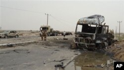 Soldiers stand by a burned out military vehicle at the site of an attack in Aden, Yemen, July 24, 2011. A suicide attacker driving a pickup truck packed with explosives blew himself up outside an army camp in Yemen's coastal city of Aden, killing at least