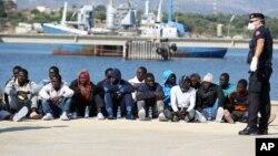一批來自非洲的船民在意大利西西里島的一個港口等待接受檢查。