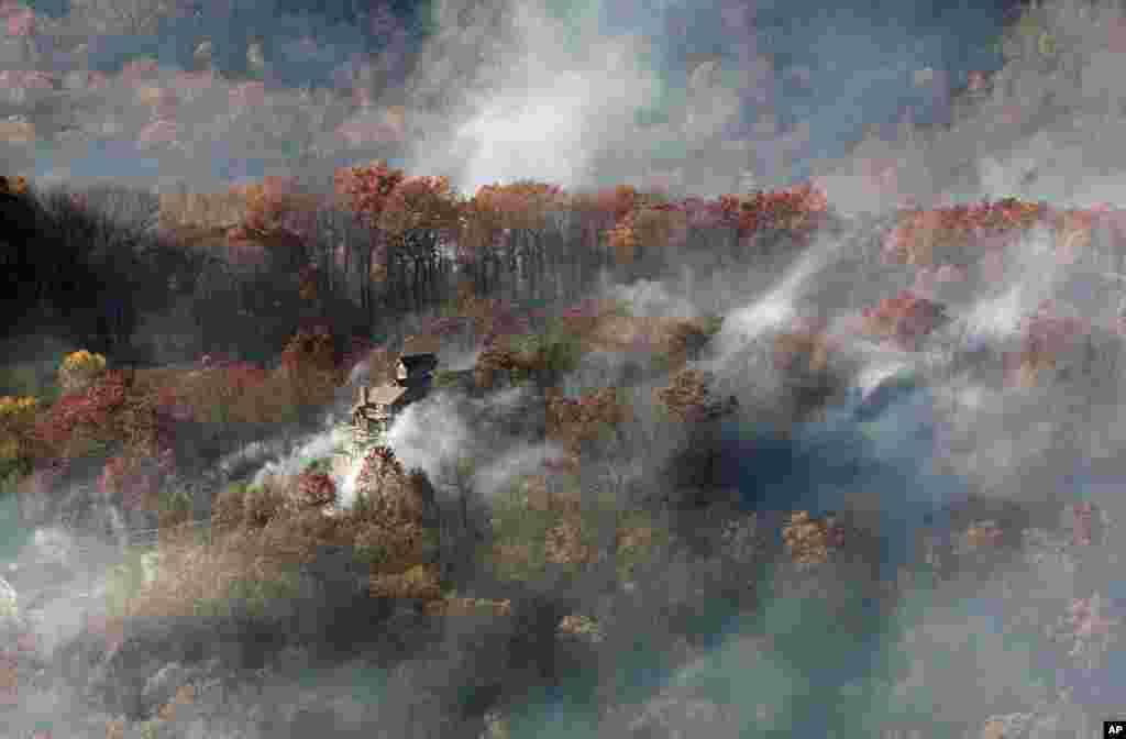 ផ្សេងហ៊ុមព័ទ្ធផ្ទះមួយក្នុងរូបភាពមួយថតពីឧទ្ធម្ភាគចក្រ National Guard ជិតក្រុង Gatlinburg រដ្ឋ Tennessee កាលពីថ្ងៃទី២៩ ខែវិច្ឆិកា ឆ្នាំ២០១៦។ មនុស្សរាប់ពាន់នាក់បានរត់ភៀសខ្លួនចេញពីភ្លើងចេះភ្លើងដ៏ប្រល័យមួយដែលបានបំផ្លាញផ្ទះរាប់រយខ្នង និងរមណីយដ្ឋានក្នុងតំបន់ Great Smoky Mountains។