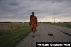 Buddhist monk Sutham Nateetong walks along the road outside Arcola, IN. June 8, 2019.