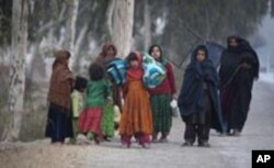 Displaced flood victims in Pakistan carry donated items by passing vehicles ahead of the winter weather.