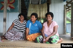 Villager Biusalia Tevita (C) poses for photo in her home for the Thomson Reuters Foundation with village nurse Seruwaia Kula (L), and a neighbor at Wailotua Village No. 1, an inland community of about 200 people that is prone to flooding, cyclones and landslides, about 65 km (40 miles) north of Suva, Fiji, Dec. 8, 2017.