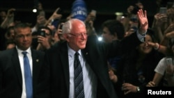 Kandidat capres AS dari Partai Demokrat, Bernie Sanders melambaikan tangan kepada para pendukungnya di Miami, Florida, pada malam menjelang pemilihan di negara bagian Michigan, Mississippi (8/3).