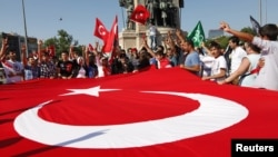 Demonstrators wave a huge national flag as they shout slogans in support of the Turkish military in central Istanbul, June 24, 2012.